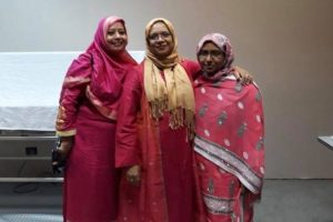 Three women smile at the camera. They are wearing colourful pink and red dresses and headscarves.