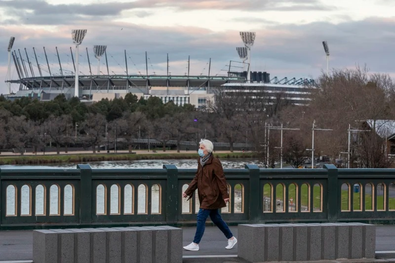 A woman wearing a mask walks along a bridge as she walks past the MCG in August.Credit:AP